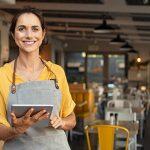 mulher na entrada do restaurante com tablet explica como trocar o sistema de gestão do restaurante