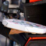 entregador tirando a pizza da caixa representa como funciona a central de delivery